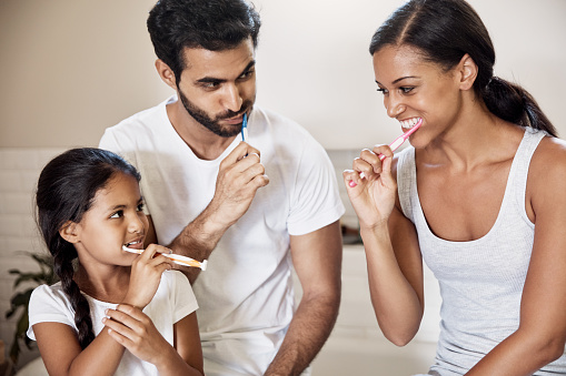 A Palo Alto family practicing proper brushing and flossing techniques to improve lifelong oral health