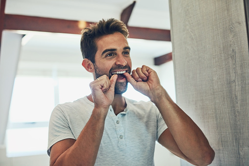 Palo Alto man flossing to prevent gum disease and promote total health